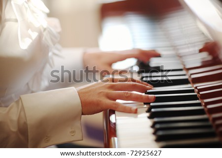 Female hands playing piano. Closeup, shallow DOF.