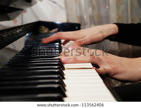 Female hands playing the old piano, close up
