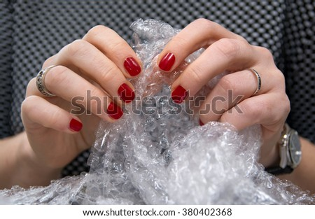 Female hands popping the bubbles in bubble wrap. Selective focus, close up.