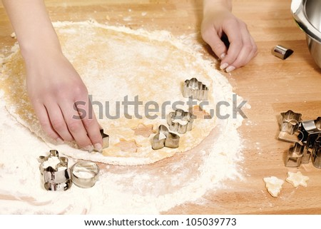 female hands pressing christmas molds in dough