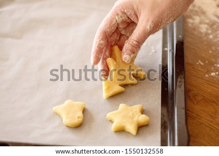 Female hands put the dough on baking tray for baking cookies. Close up. #1550132558