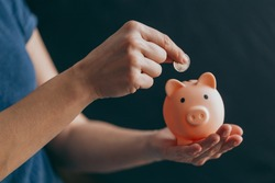 female hands puts a coin in a pink piggy bank. The concept of saving money or savings, investment