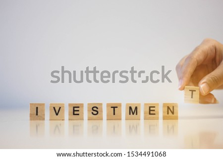 Female hands putting wooden cube text for investment word -  Investment Concept
