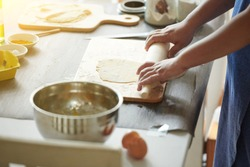 Female hands roll out a piece of dough with a rolling pin for making ravioli or dumplings on a wooden table sprinkled with flour. A step-by-step recipe for cooking ravioli or dumplings