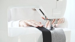 Female hands sew on a white sewing machine close-up. Concept of sewing in modern bright studio, woman in white sweater sewing grey cloth in process, selective focus