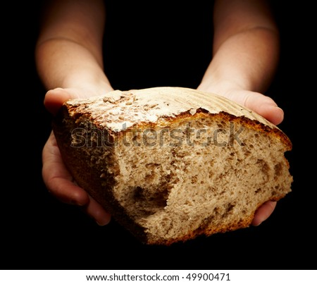 female hands sharing a sliced loaf of bread