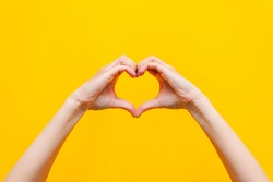 Female hands showing a heart shape isolated on a bright color yellow background. Sign of love, harmony, gratitude, charity. Feelings and emotions concept