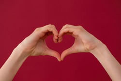 Female hands showing heart sign on red background in studio. Fingers illustrating gesture of love on burgundy backdrop. Valentine theme expressed in symbol.