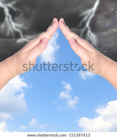 Female hands showing protection sign with the storm sky outside and blue sunny sky inside. Protection concept.
