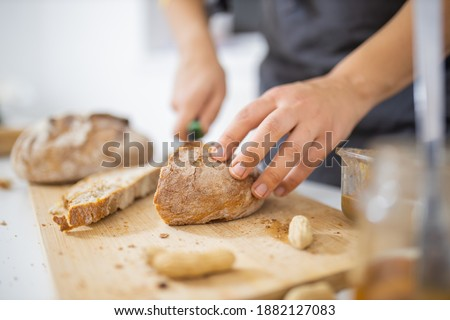 Female hands slicing bread on wooden cutting board. Woman carefully cutting sourdough bread above white table. Healthy meal preparation Stockfoto ©