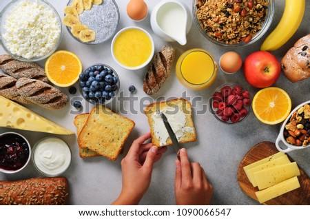 Female hands spreading butter on bread. Woman cooking breakfast. Healthy breakfast ingredients, food frame. Granola, egg, nuts, fruits, berries, milk, yogurt, juice, cheese. Top view, copy space.