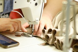 Female hands stitching white fabric on professional manufacturing machine at workplace. Close up view of sewing process. Light blurred background
