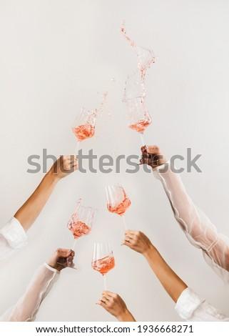 Female hands swirling glasses of rose wine making splashes Stockfoto ©