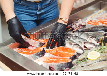 Female hands take salmon steak from showcase. Fish food at shop, close up. Raw fish ready for sale in the supermarket. Showcase with chilled red fish in grocery store. Market place with sea food.