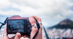 Female hands taking a photo of Athens with a digital camera