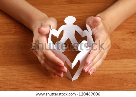 Female hands taking care of paper people, isolated on grey