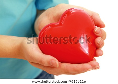 Female hands taking care of red heart symbol isolated on white background