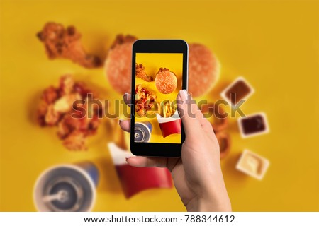 Female hands taking photo of tasty burger with snacks on table