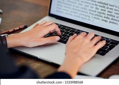 Stock photo of female hands touching keyboard of laptop with words on screen. Crop office worker typing document using modern gadget. Concept of business