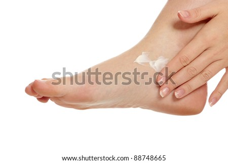 Female hands treating feet with moisturizing cream, isolated on white