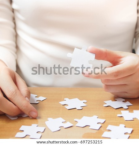 Female hands trying to connect pieces of white jigsaw puzzle on wooden table. Creative idea for anxiety, confusion, stress, depression, thinking and problem solving concept. Square. Copy space. #697253215