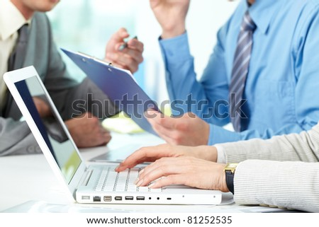 Female hands typing among working businesspeople