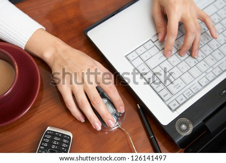 Female hands typing on a laptop
