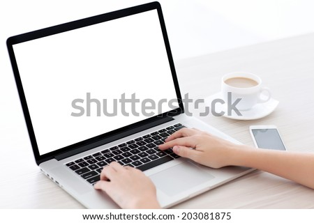 Female hands typing on a laptop keyboard with isolated screen in a white room on a desk with a phone and a cup of coffee #203081875
