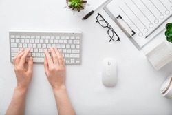Female hands typing on keyboard at white table workplace. Home office workspace with keyboard mouse glasses. Flat lay woman hands on white desk use pc computer silver keyboard. Top view