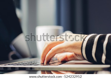 Female hands typing on keyboard of laptop, working at home concept
