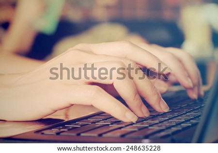 Female hands typing on laptop with retro filter effect #248635228
