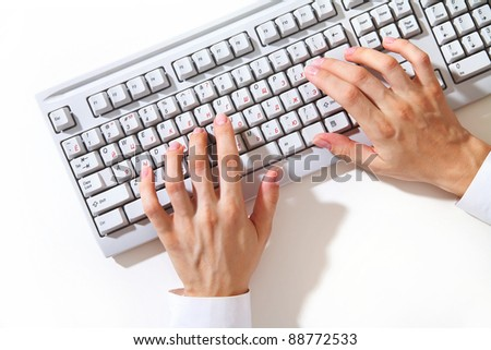 Female hands typing on white computer keyboard on white desk - stock photo