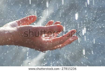 Female hands under falling clean water drops