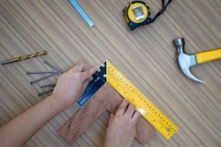 Female hands using a try square to check that the woodworking corners are square with a set collection of working hand tools for the wooden, Toolset with the do it yourself (DIY)