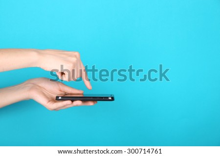Female hands using mobile phone on blue background