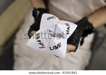 Female hands wearing lace gloves playing a game with folded paper - stock photo