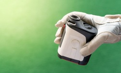 Female hands wearing professional glove with white and black modern optical range finder used for golfing or hunting.
