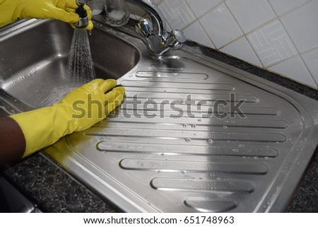 Female hands, wearing yellow rubber gloves, cleaning the sink #651748963