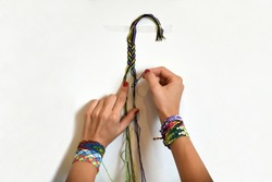 Female hands weaving knot for DIY friendship bracelet Pigtail. Many handmade bracelets on girls wrists. Friendship bracelet making process, step by step. White background with copy space