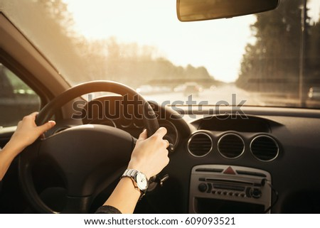 Female hands with a clock on the steering wheel of a car while driving. Against the background, the windshield and road
