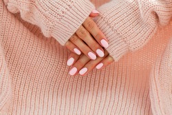 Female hands with beautiful oval-shaped nails, matte pink manicure close-up on a pink knitted sweater background. Shellac. Copy space