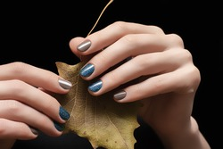 Female hands with blue gray nail design. Glitter blue nail polish manicure. Female hands hold autumn leaf