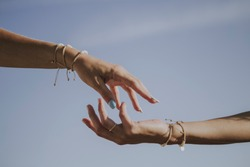 female hands with bracelets that are about to touch with the blue sky in the background