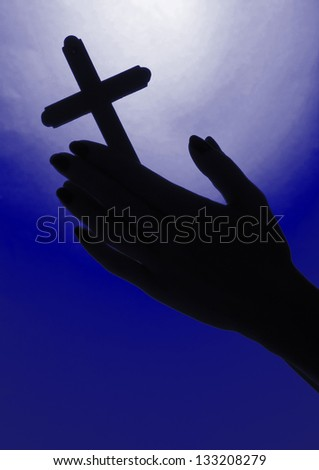 Female hands with crucifix, on bright blue background