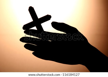 female hands with crucifix, on brown background