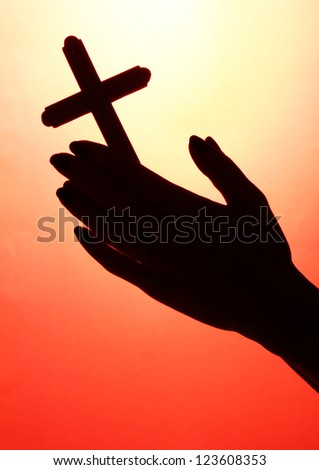 female hands with crucifix, on red background - stock photo