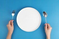 Female hands with cutlery and empty plate on blue background. Meal preparation concept. Top view