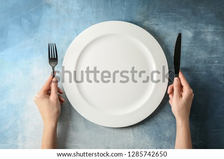 Female hands with cutlery and empty plate on color background