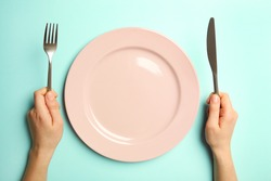 Female hands with cutlery and empty plate on turquoise background