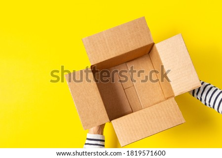 Female hands with empty open cardboard boxes on yellow background. Top view Foto stock ©
